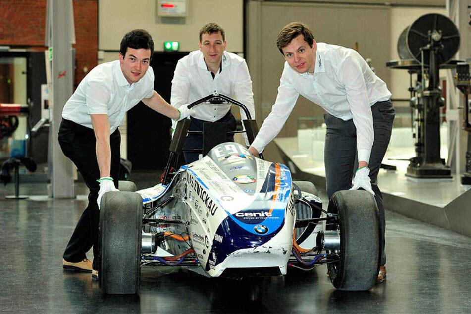 Maximilian Pöhlmann (25), Thomas Ganzer (33) und Projektleiter Manuel Seifert  (21) schieben den Rennwagen in die Ausstellung.