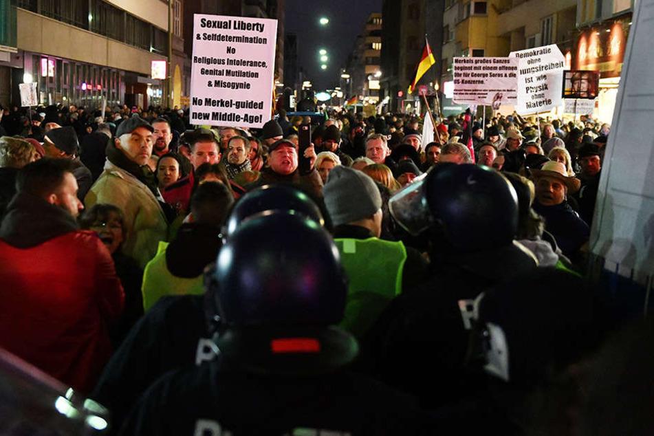 """Polizisten stehen bei dem """"Frauenmarsch"""" aus dem AfD-Umfeld nahe dem Checkpoint Charlie in einer Kette vor den rechten Demonstranten."""