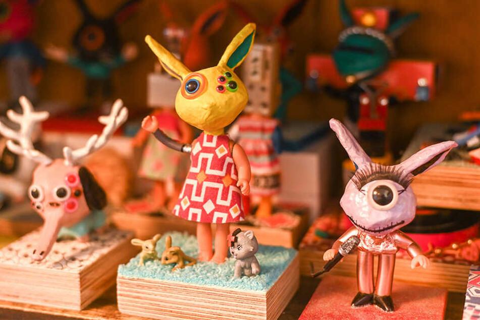 Schöne bunte Trash-Welt: Auf den Körpern von Puppen und Actionfiguren sitzen lackierte und beklebte Hasenköpfe aus Pappmaschee.