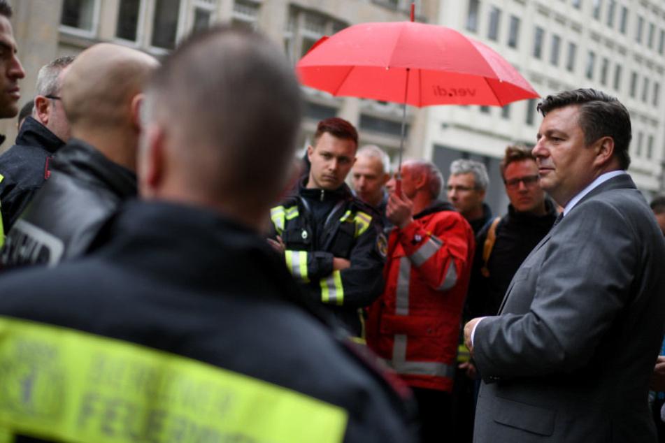 Andreas Geisel (SPD), Innensenator von Berlin, unterhält sich mit Teilnehmern einer Protest-Mahnwache der Feuerwehr. (Archivbild)