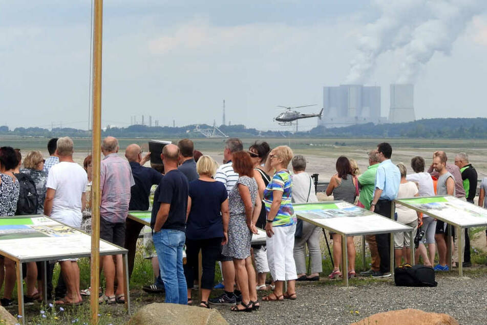 Am Aussichtspunkt des Tagebaus Vereinigtes Schleenhain sehen Schaulustige der Hubschrauberbesatzung bei der Arbeit zu.