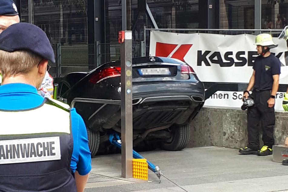 Einsatzkräfte der Feuerwehr betrachten einen Mercedes, der die Treppe eines U-Bahn-Eingangs in München hinuntergefahren ist.