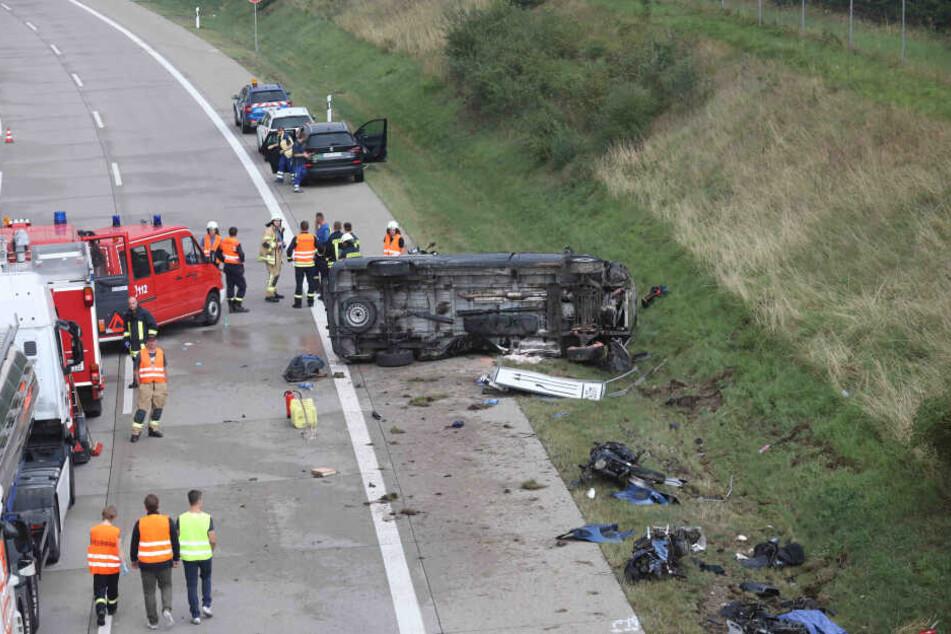 Einsatzkräfte stehen an der Unfallstelle auf der A9 neben dem Kleintransporter. Bei dem Unfall kamen vier Menschen ums Leben.