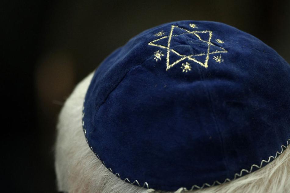 Ein Mann trägt in einer Synagoge eine Kippa mit einem aufgenähtem Stern.