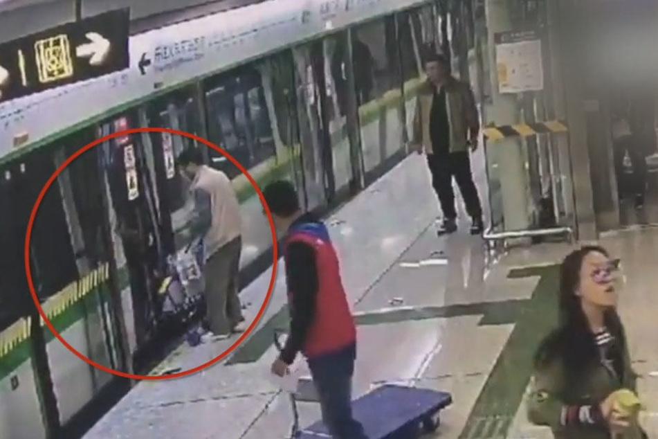 Der Mann versucht, die Tür offen zu halten, indem er den Buggy einklemmt.