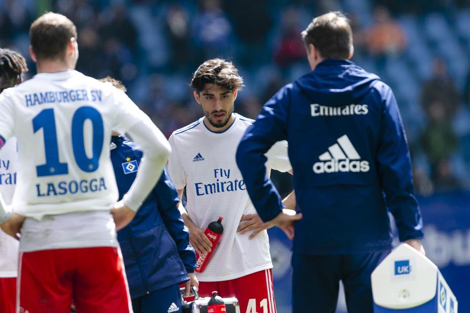 Berkay Özcan steht zwischen seinen Mitspielern auf dem Spielfeld.