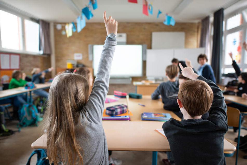 Schüler einer fünften Klasse eines Hamburger Gymnasiums melden sich im Unterricht.