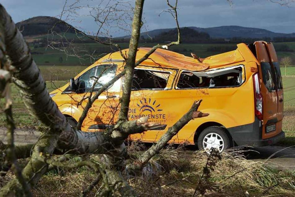 Ein Schul-Minibus steht in Deute (Hessen) zerstört am Straßenrand, nachdem er zuvor von einem im Sturm umstürzenden Baum getroffen wurde.