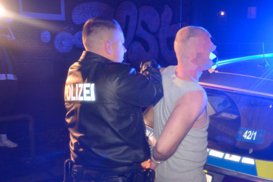 Ein Polizist nimmt den 38-Jährigen vor seinem Wohnhaus fest.