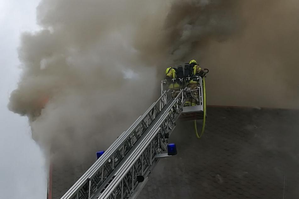 Einsatzkräfte bekämpfen die Flammen aus dem Korb einer Drehleiter.