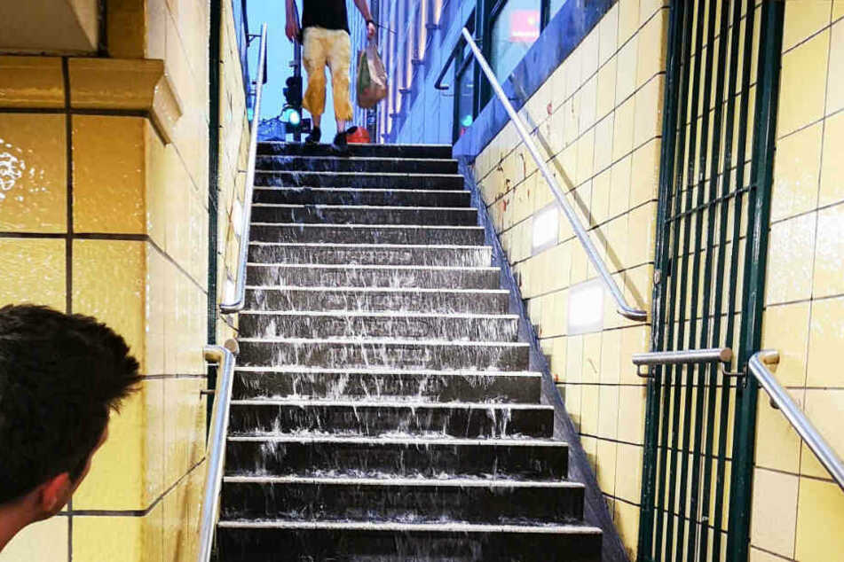 Nach schweren Regenfällen läuft Wasser die Stufen zum U-Bahnhof Friedrichstraße runter.