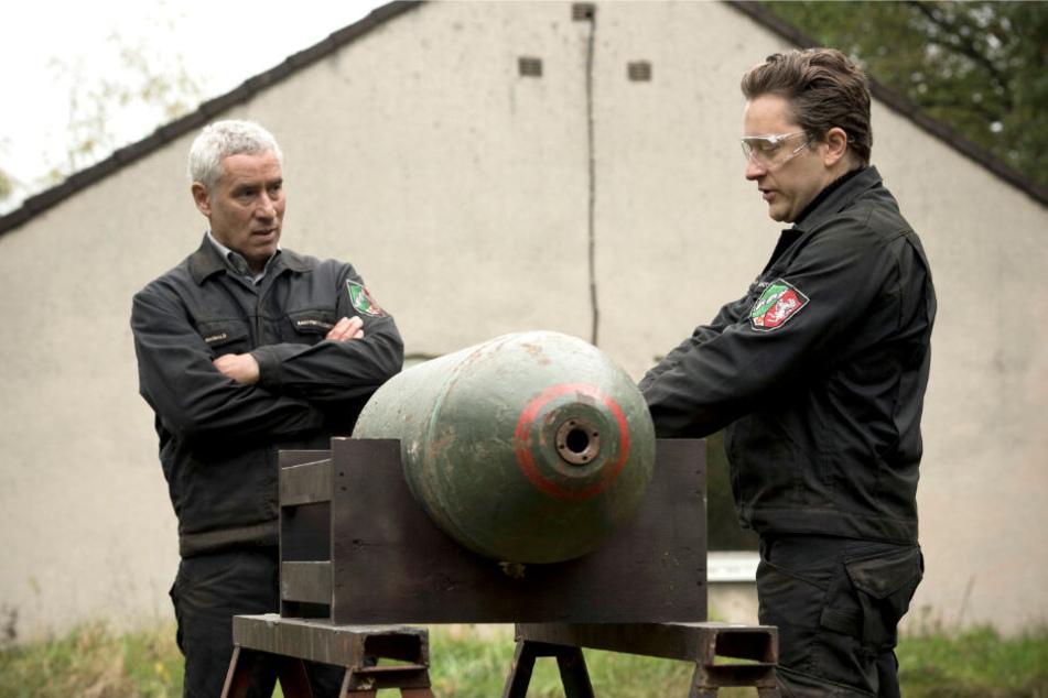 Maiwald (Ralph Herforth,, li.), der Leiter der Dienststelle des Kampfmittel-Räumdienstes, und sein Sohn und Kollege Joachim (Adrian Topol) üben mit einer Bomben-Attrappe.