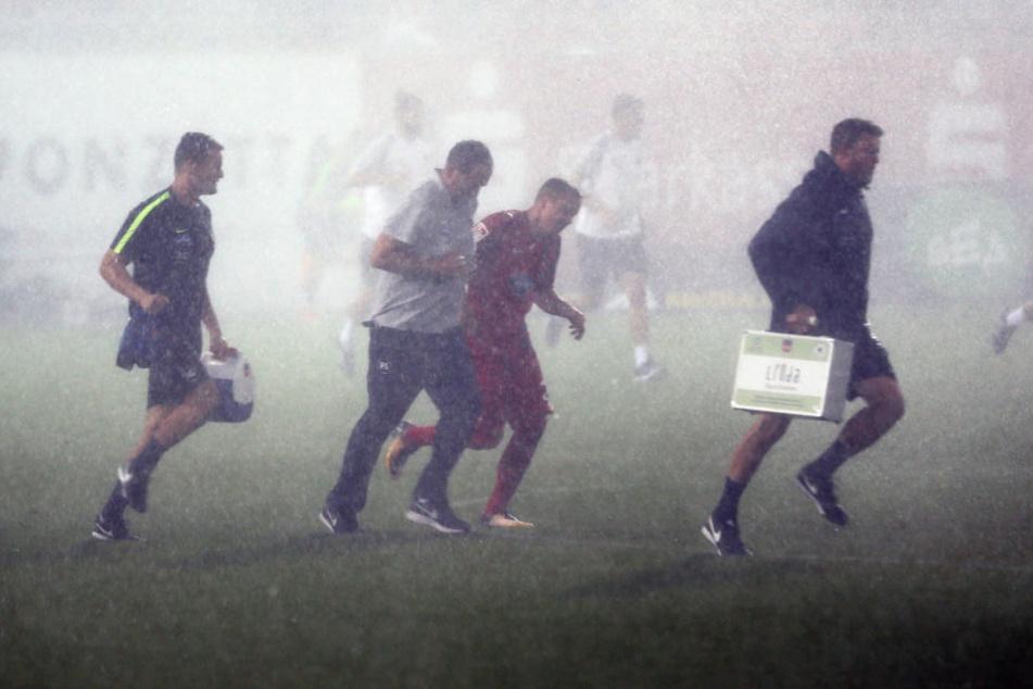Ab in die Kabine! Spieler und Betreuer versuchen verzweifelt dem Regen davonzurennen.