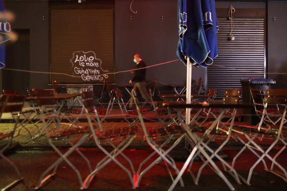 Ein Mann geht an einer geschlossenen Gaststätte vorbei. Zur Eindämmung der Corona-Pandemie werden Gastronomiebetriebe vom 2. November für den restlichen Monat geschlossen.