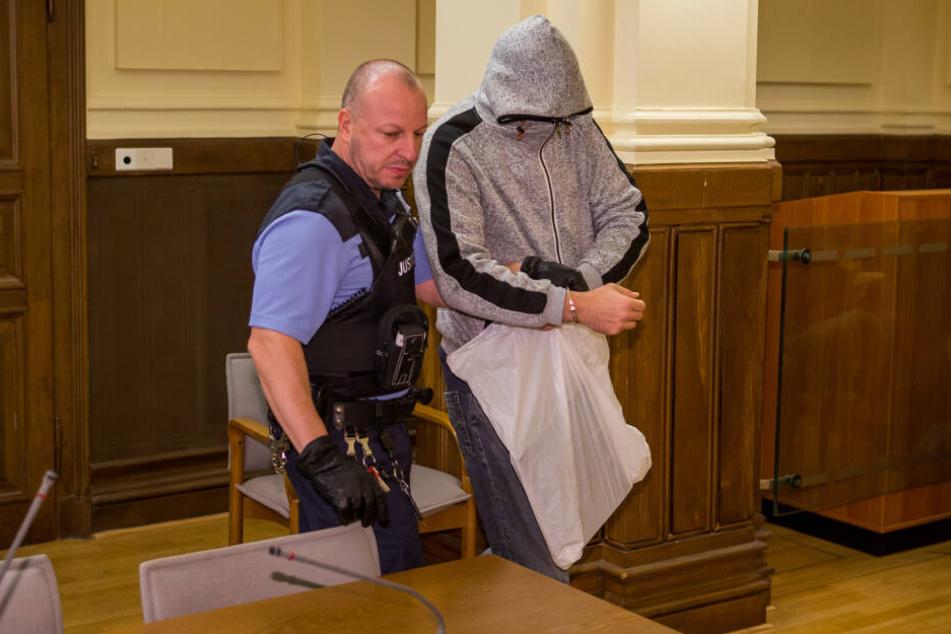 Mit tief ins Gesicht gezogener Kapuze lässt sich Kinderschänder Robert G. (39) von einem Justizbeamten in den Gerichtssaal führen.