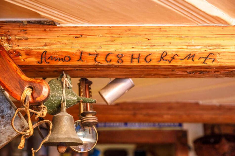 Am freigelegten Balken über der Theke sieht man deutlich das Baujahr des Hauses und die beteiligten Zunftzeichen.