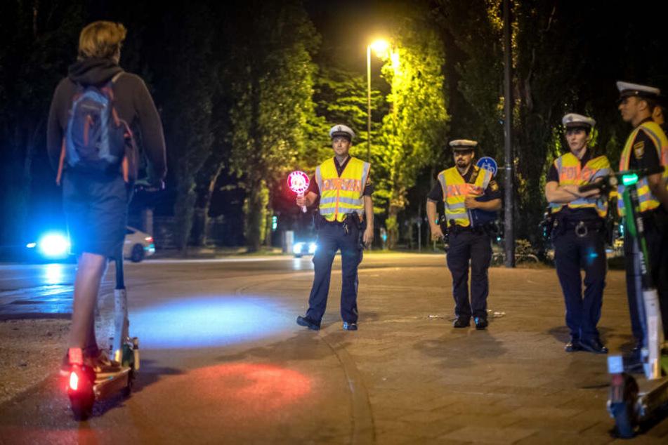 Polizisten kontrollieren einen E-Scooter-Fahrer.