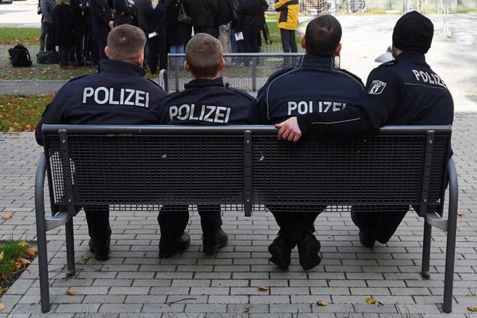 Polizeischüler sitzen auf dem Gelände der Akademie auf einer Bank.