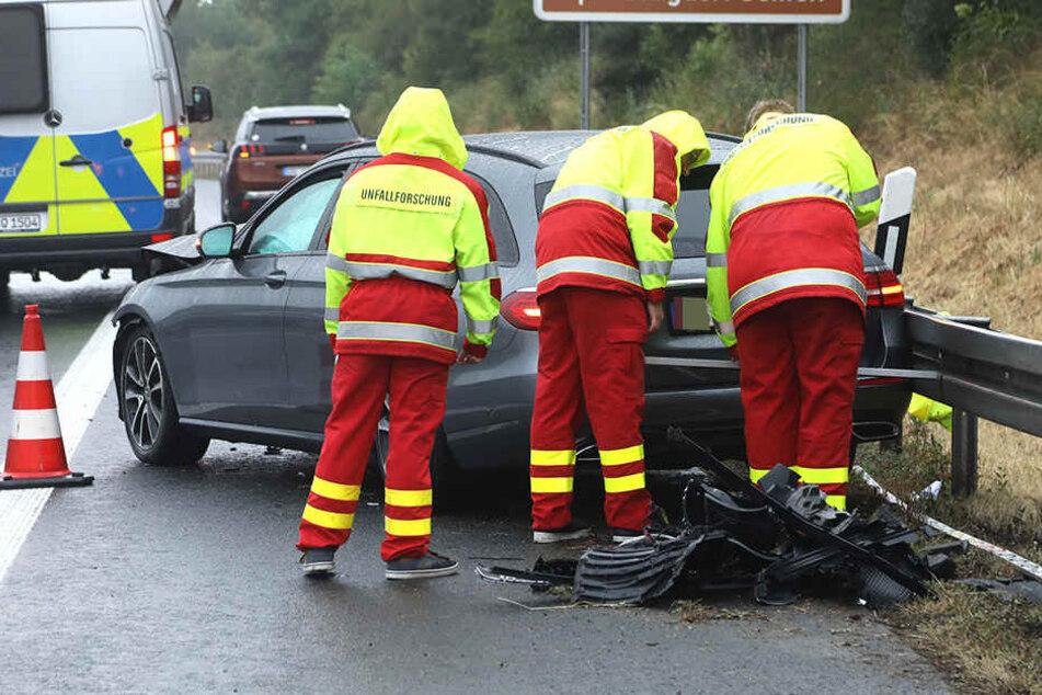 Mitarbeiter der Unfallforschung begutachten das gegen die Leitplanke gefahrene Fahrzeug.