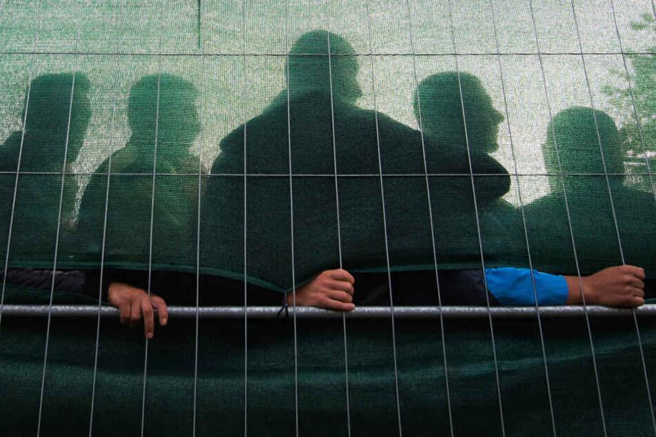 Männliche Flüchtlinge stehen in einer Unterkunft in Hamburg-Jenfeld hinter einem Zaun.