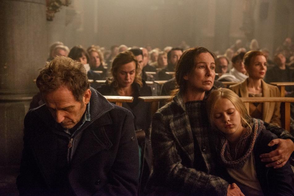 Michel Desmedt (l., Charles Berling), Jeanne (Murielle Texier) und die junge Emilie (Pauline Sakellaridis) hoffen in der Kirche auf ein Wunder. Dass Remí zu diesem Zeitpunkt schon tot ist, wissen sie nicht.