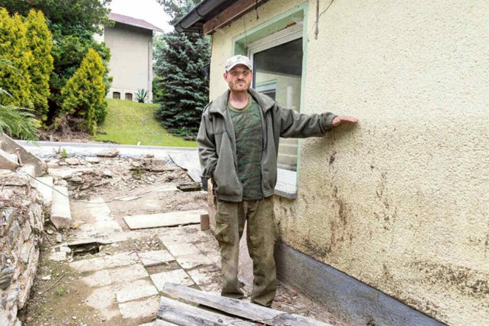 Rene Witt (47) zeigt, wie hoch das schlammige Wasser an seinem Haus stand.