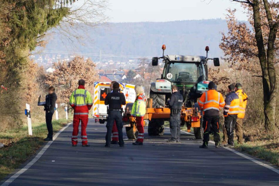 Einsatzkräfte stehen vor dem Traktor.