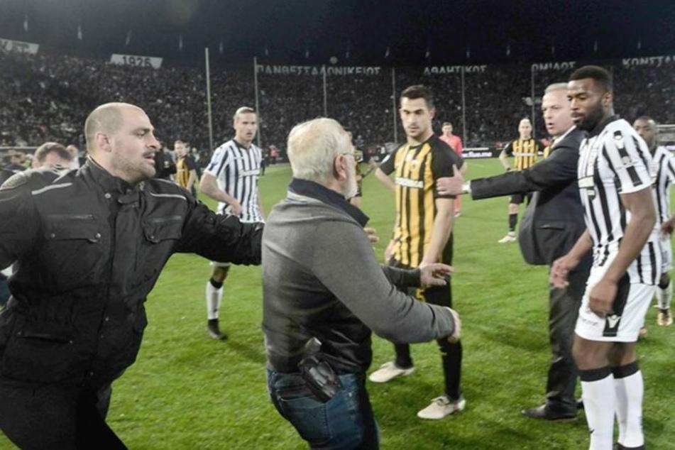 Eine Szene zeigt, wie der Besitzer und Präsident von Paok Saloniki mit einer Waffe auf Spieler losgeht.
