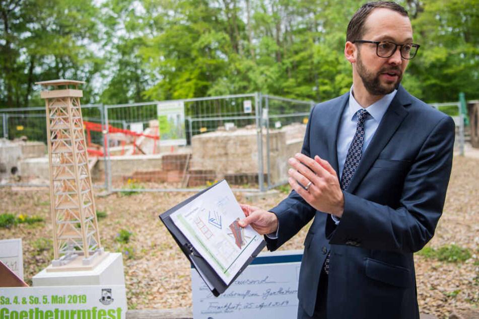 Jan Schneider, Baudezernent der Stadt Frankfurt, zeigt neben dem Holzmodell des neuen Goetheturms die Pläne für den Wiederaufbau.