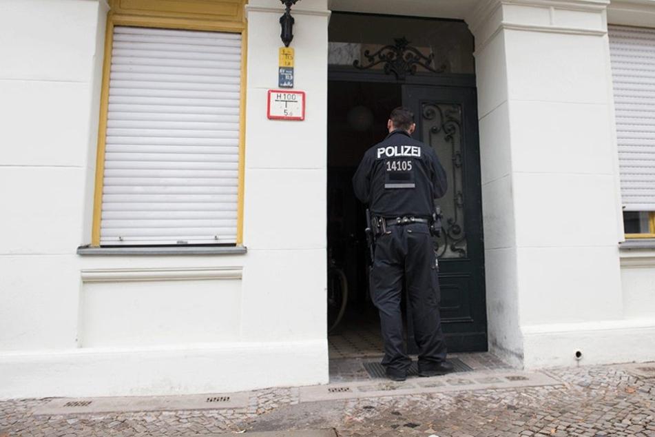 Ein Polizist steht im Eingang des Hauses, in dem die Bluttat geschah.