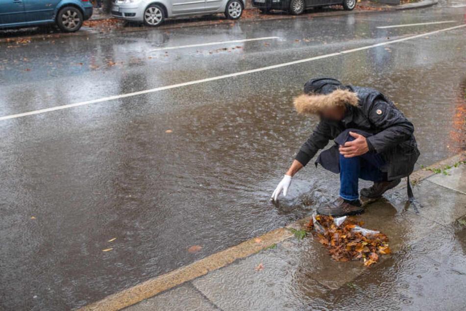 Eine Person befreit einen verstopften Abfluss vom Laub.
