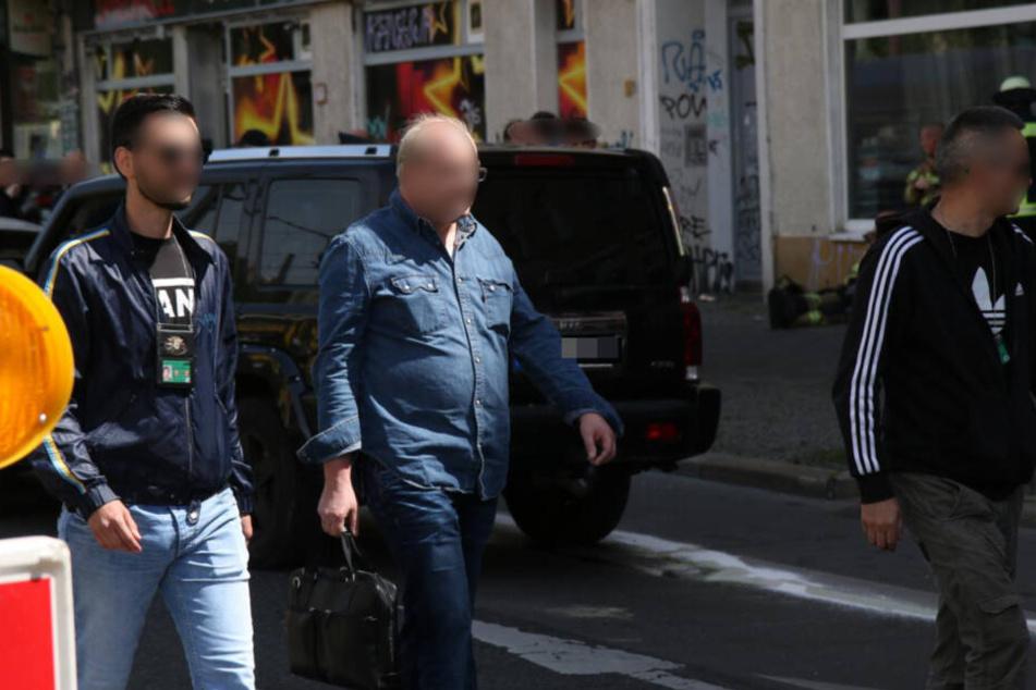 Der Verdächtige (Mitte) wird von Zivilpolizisten festgenommen, in der Hand hält er noch seine Aktentasche.