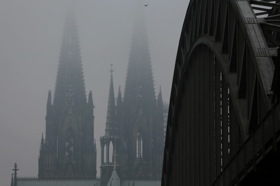 Die Spitzen des Domes verschwinden hinter der Hohenzollernbrücke im Nebel.