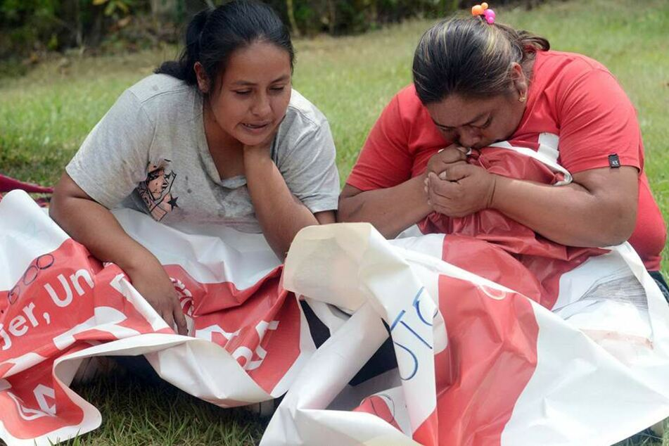 Verwandte der Bürgermeisterkandidatin Karina Garcia (†32), die in der Nacht tot aufgefunden wurde, halten ihr politisches Banner und weinen.