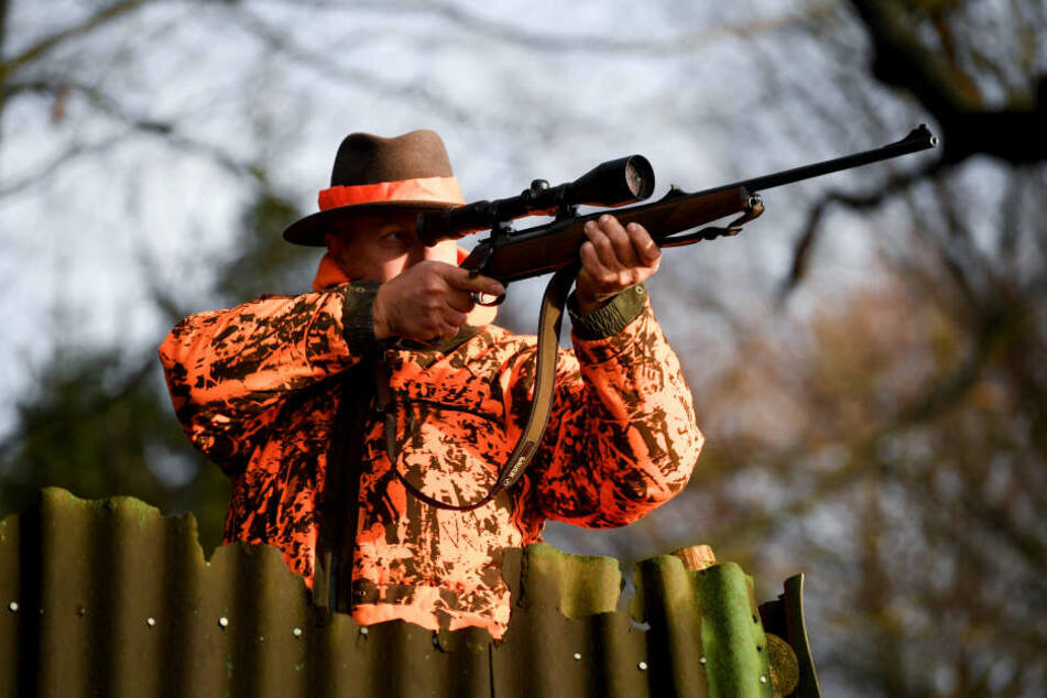 Ein Jäger steht mit dem Gewehr im Anschlag auf einem Feld.