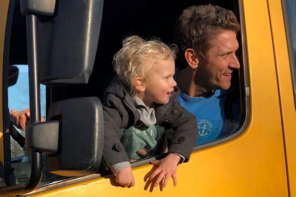 Peer Kusmagk (r) sitzt mit seinem Sohn Emil-Ocean in einem Umzugswagen.
