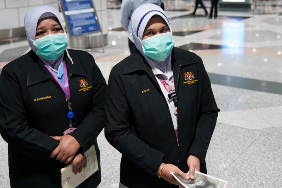 Personal der Gesundheitsbehörde steht mit Mundschutz, als Schutzmaßnahme gegen die Verbreitung der neuartigen Lungenkrankheit durch den Corona-Virus, während einer Inspektion am Flughafen Kuala Lumpur International Airport.