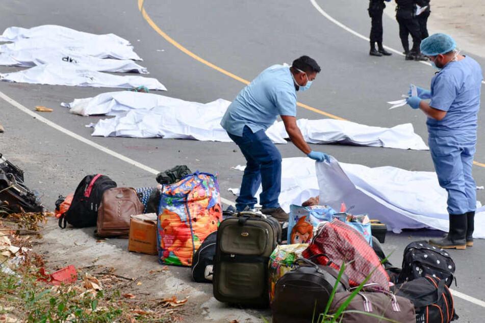 Forensische Mitarbeiter decken Leichen von verstorbenen Passagieren ab.