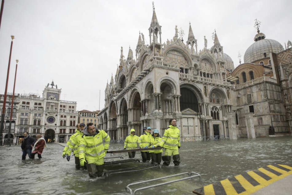 Arbeiter der Gemeinde tragen Holzplatten, um einen Steg über das Hochwasser des überfluteten Markusplatzes zu bauen.