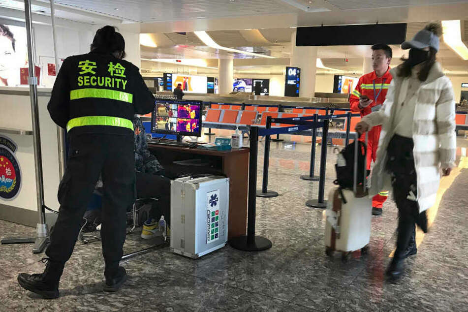 Eine Reisende trägt einen Mundschutz am Flughafen Wuhan Tianhe International Airport und geht an einem Posten vorbei, an dem Reisende auf erhöhte Temperatur überprüft werden.