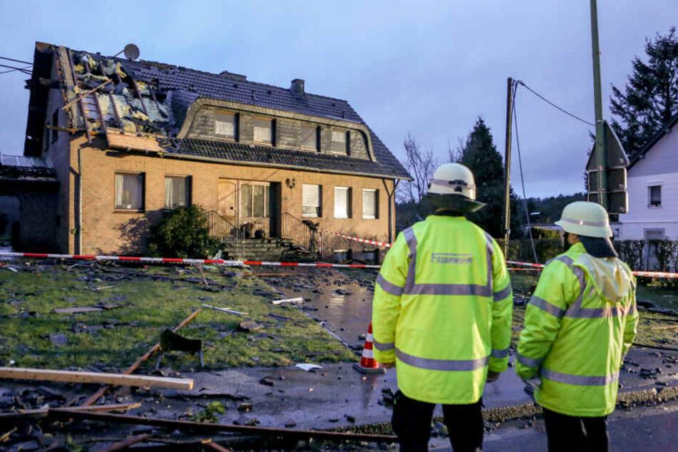 Mitglieder der Feuerwehr stehen vor einem Haus, dessen Dach schwer beaschädigt wurde.