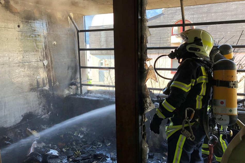 Die Feuerwehr löscht die schwer beschädigte Wohnung.
