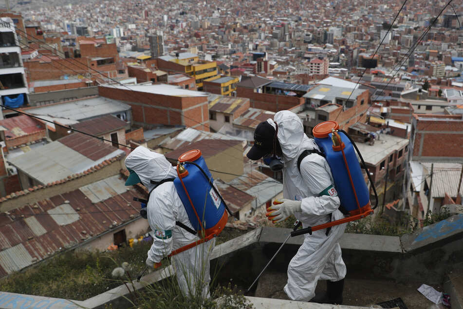 Mitarbeiter der Stadt desinfizieren in Schutzanzügen und Atemschutzmasken eine Treppe, um die Ausbreitung des Coronavirus einzudämmen. (Archivbild)