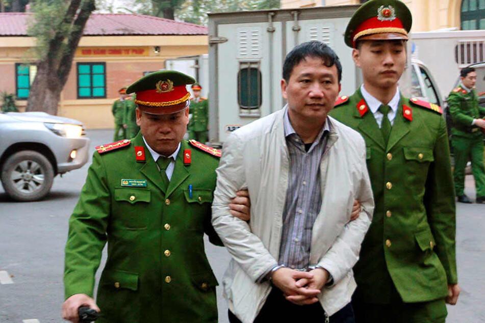 Der angeklagte Geschäftsmann Trinh Xuan Thanh (M) wird von Polizisten zu, einem Gericht in Hanoi (Vietnam) gebracht.