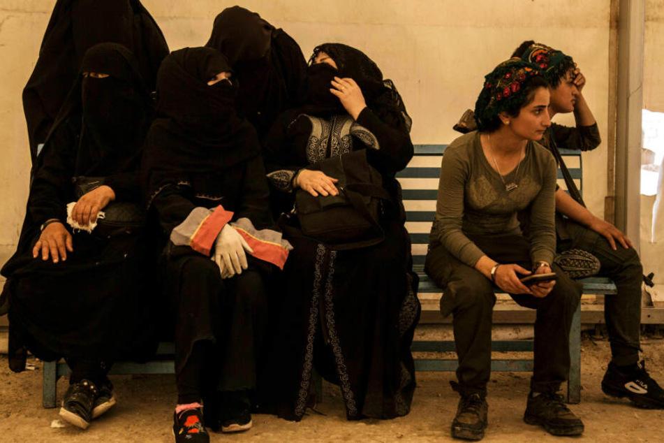 Frauen (l), die mit Kämpfern der Terrormiliz Islamischer Staat (IS) verwandt sind, sitzen im Juni neben ihren Wächterinnen.