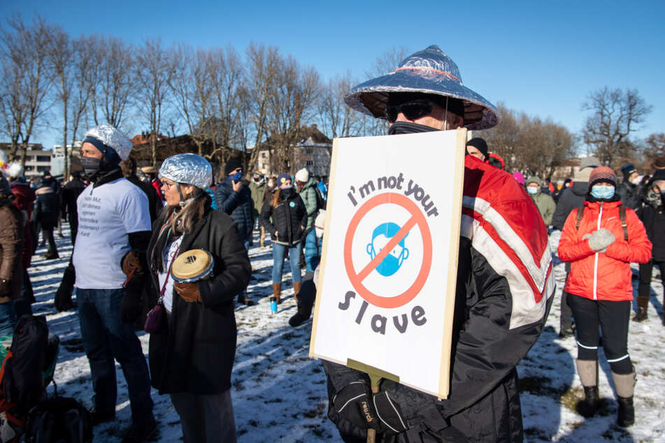 """""""I'm not your slave"""", steht auf dem Plakat eines Mannes, der einen Aluhut trägt."""