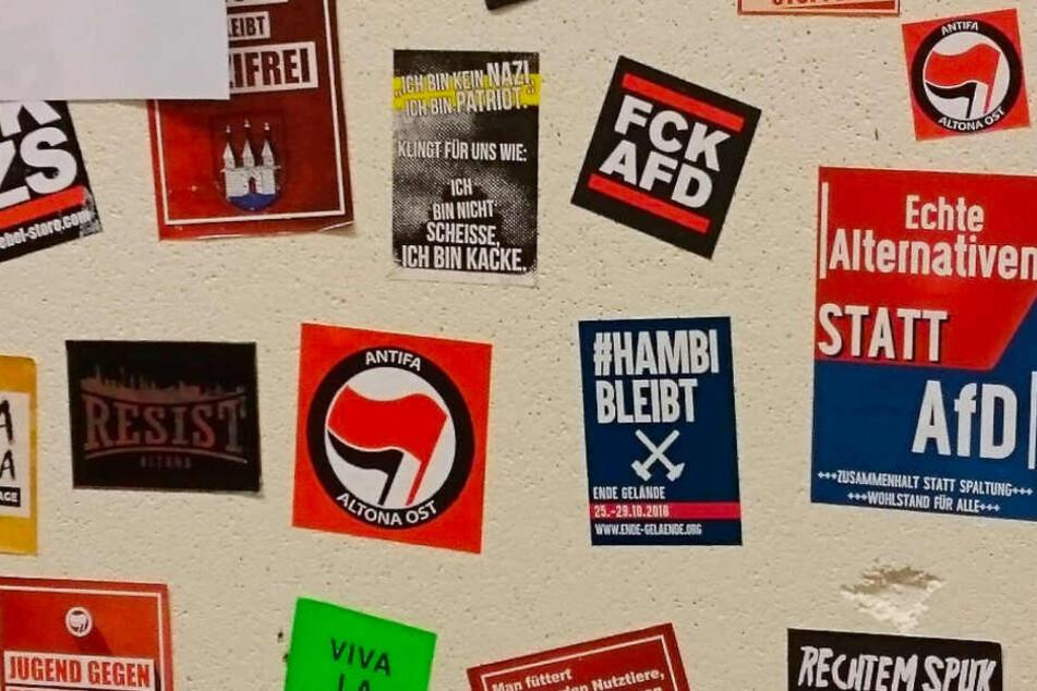 Auf einer Stellwand sind Aufkleber unter anderem von der Antifa Altona Ost und mit AfD-feindlichen Sprüchen angebracht.