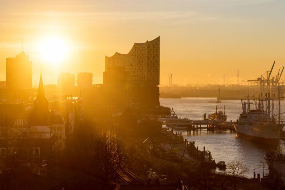 Die Sonne geht über der Elbphilharmobie und dem Hamburger Hafen auf.