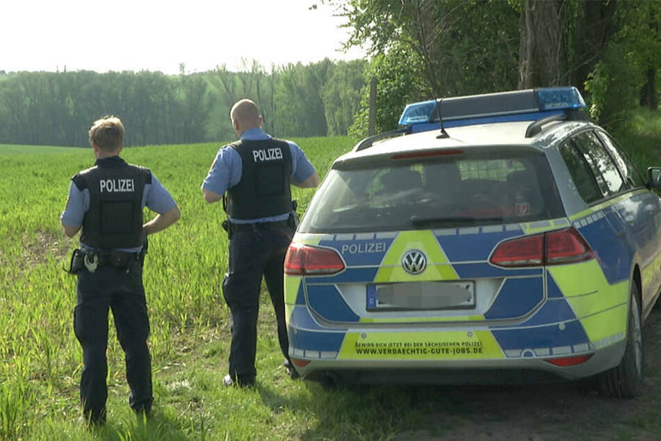 Polizisten sichern die Zufahrt zum Waldstück, in dem der tote Jäger und der Rehbock gefunden wurden.