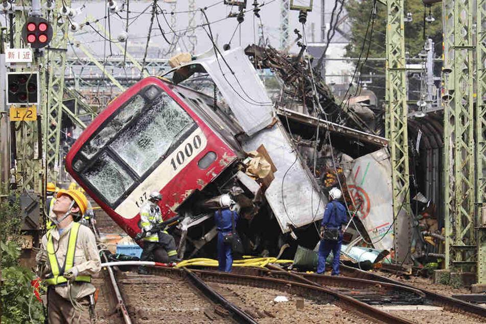 Der Zug steht entgleist nach einem Zusammenstoß mit einem Lastwagen an einem Bahnübergang auf den Gleisen.